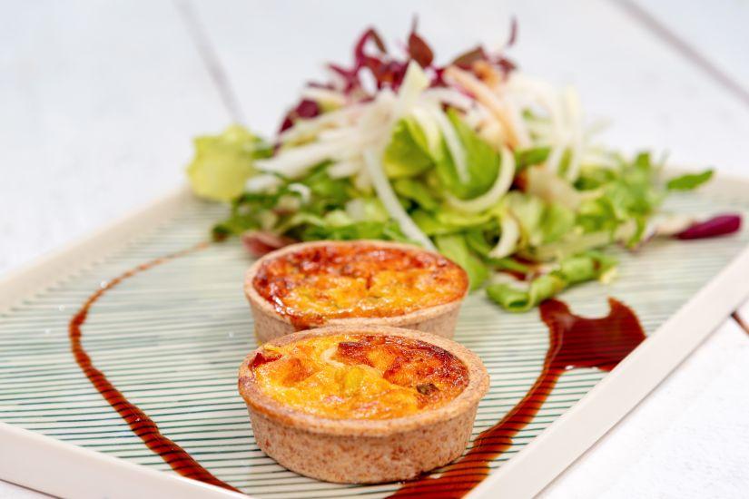 Quiche cu somon afumat, roșii uscate și ceapă verde, salată mixtă cu gulii